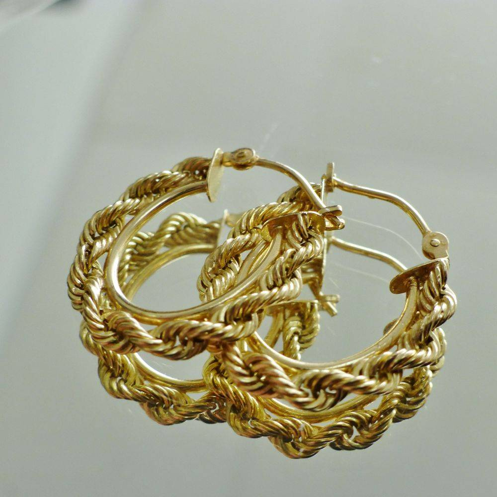 closeup picture of a pair of yellow gold twisted rope hoop earrings