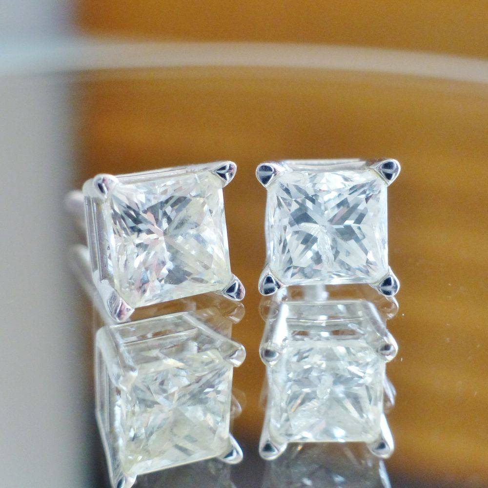 closeup picture of a pair of white gold princess cut diamond stud earrings