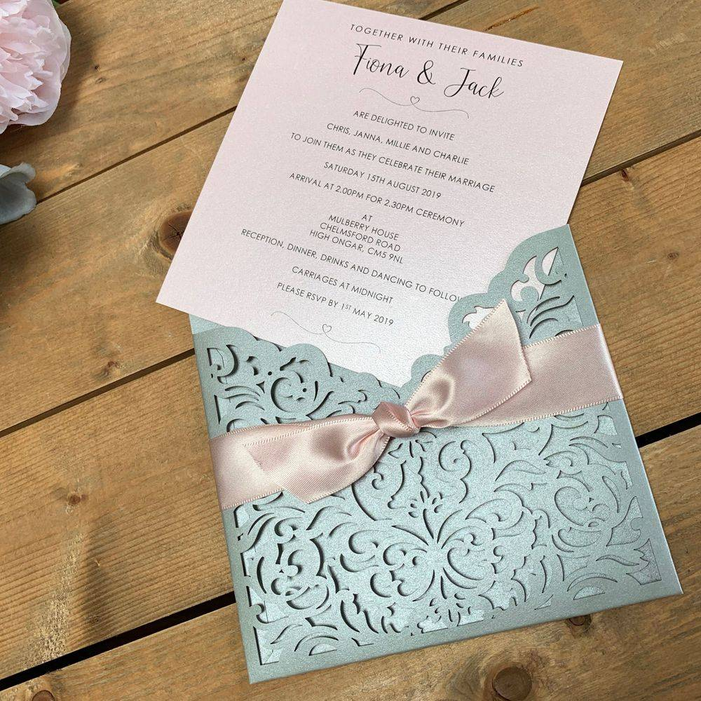 Laser cut wedding invitations in silver and pale pink