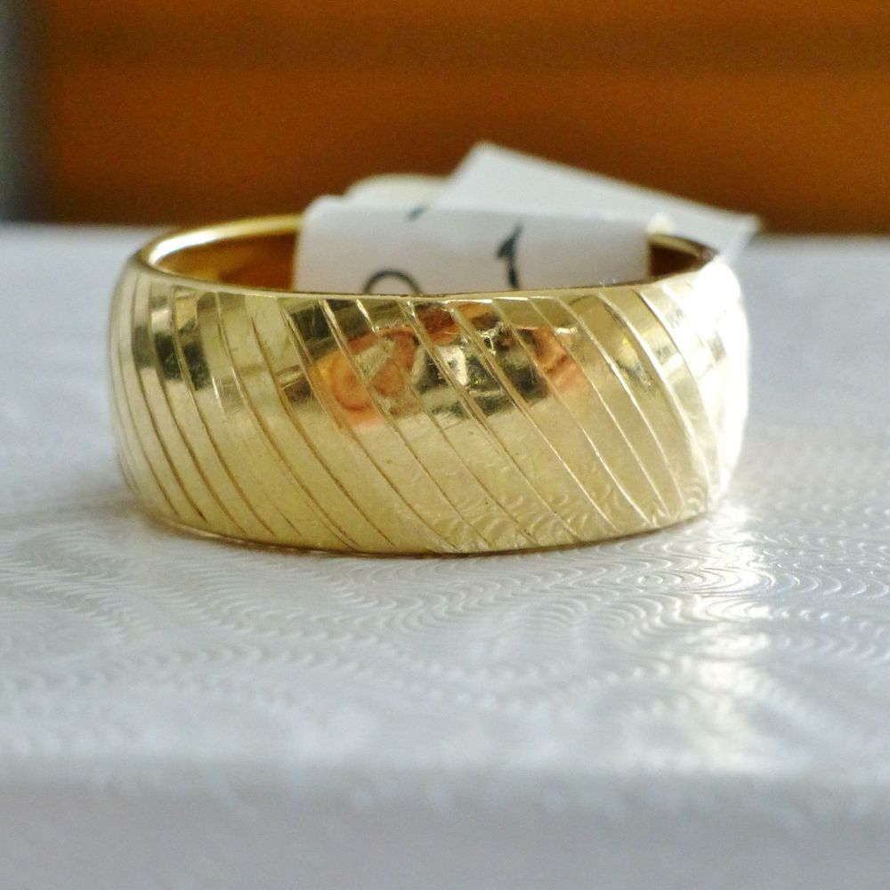 closeup picture of an 18k yellow gold diagonal stripe domed wedding ladies band