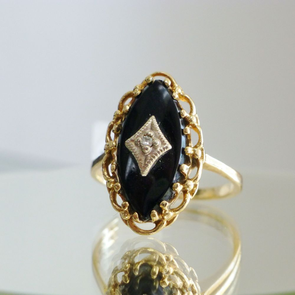 Closeup picture of a gold framed marquise shaped black onyx diamond accent ring