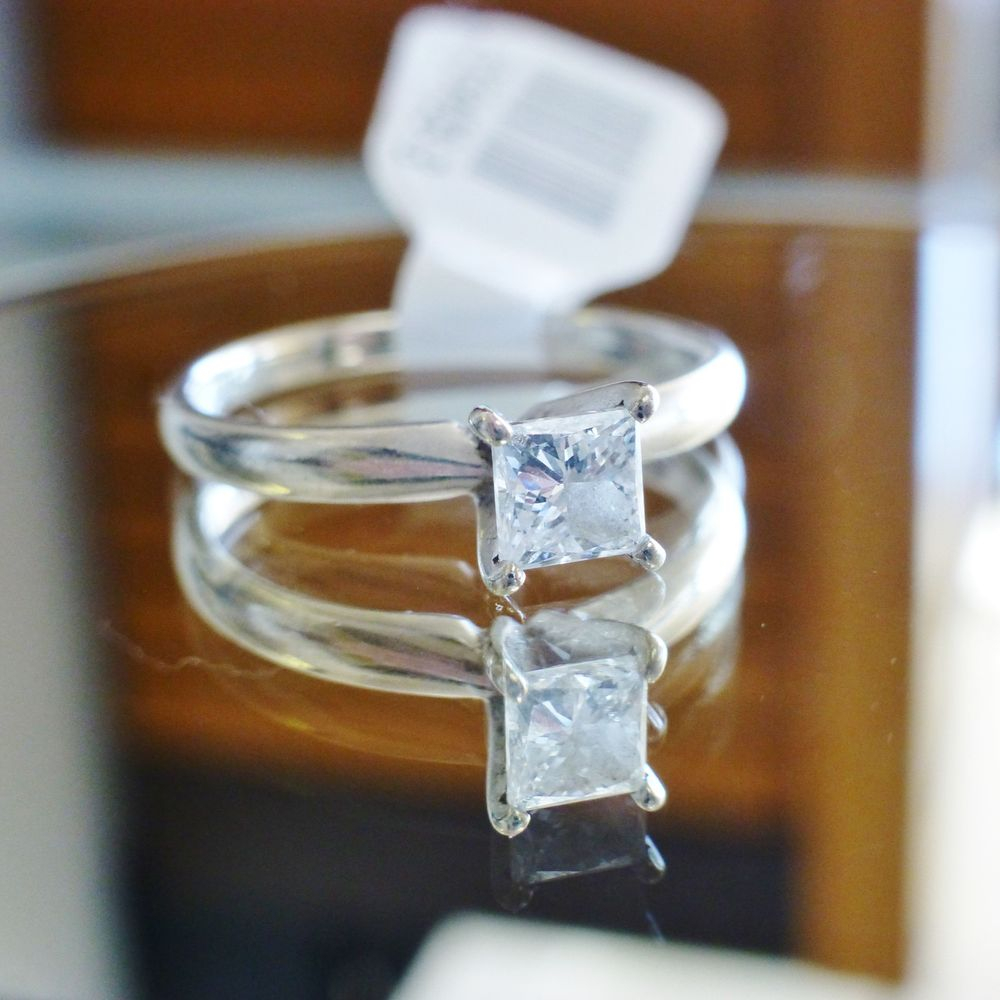 close up picture of a princess cut half carat diamond solitaire white gold ring