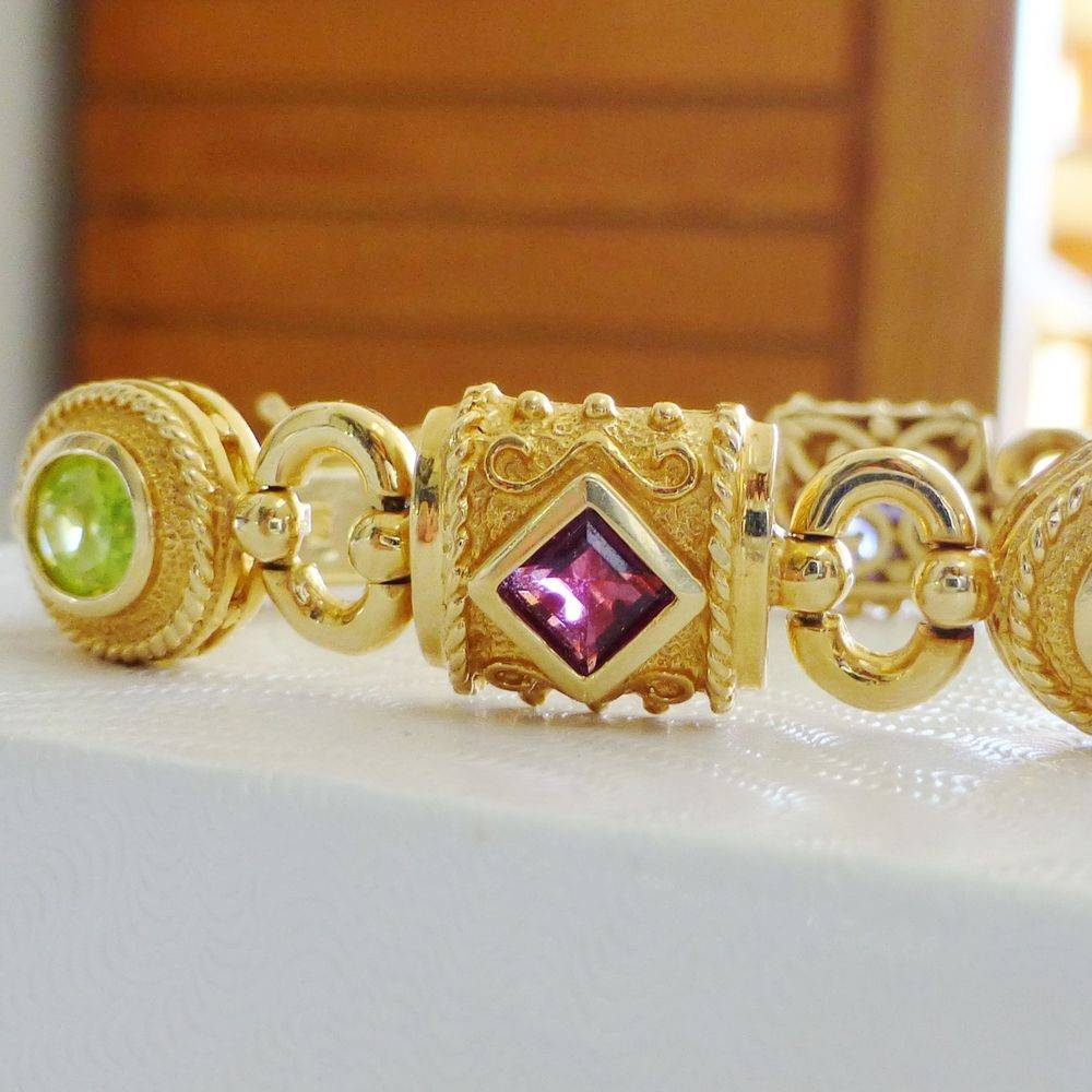 close up picture of a yellow gold bracelet with bezel set oval and princess cut multi gemstones