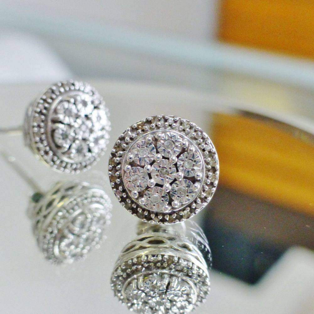 close up picture of a pair of white gold diamond composite round frame stud earrings