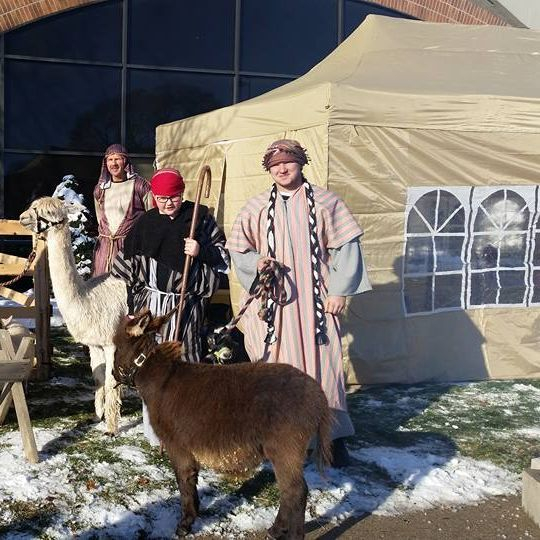 Picture of shepherds holding miniature donkey and alpaca