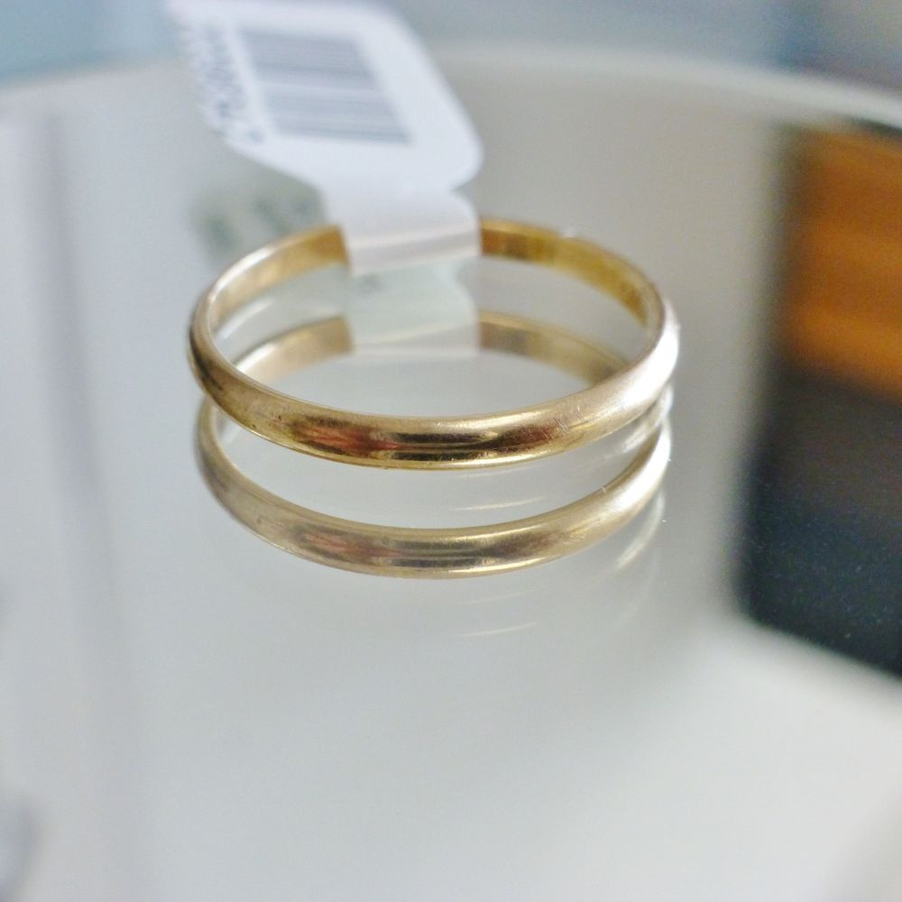 close up picture of a thin, polished ladies yellow gold wedding band
