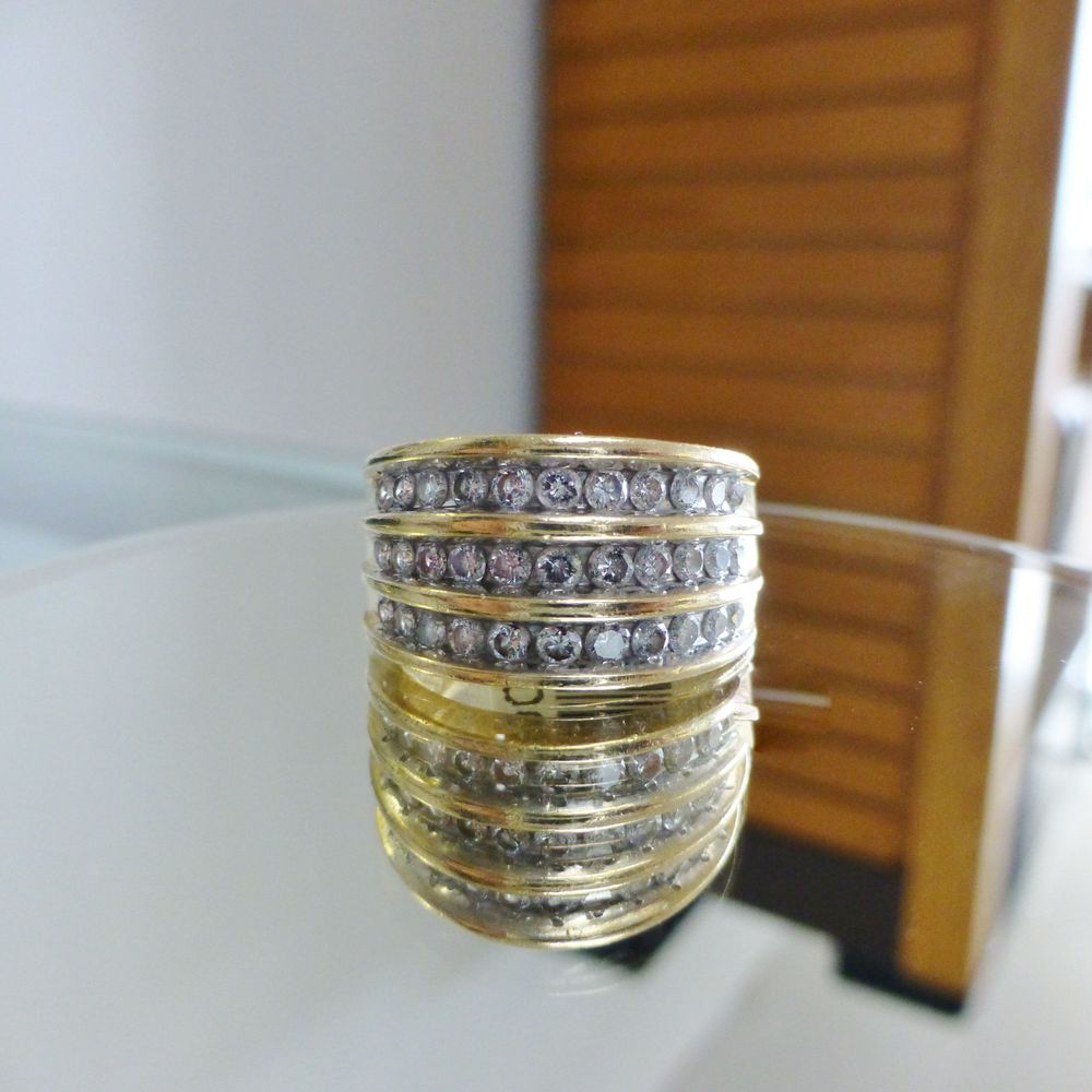 close up picture of a yellow gold triple row wedding band with channel set round cut diamonds