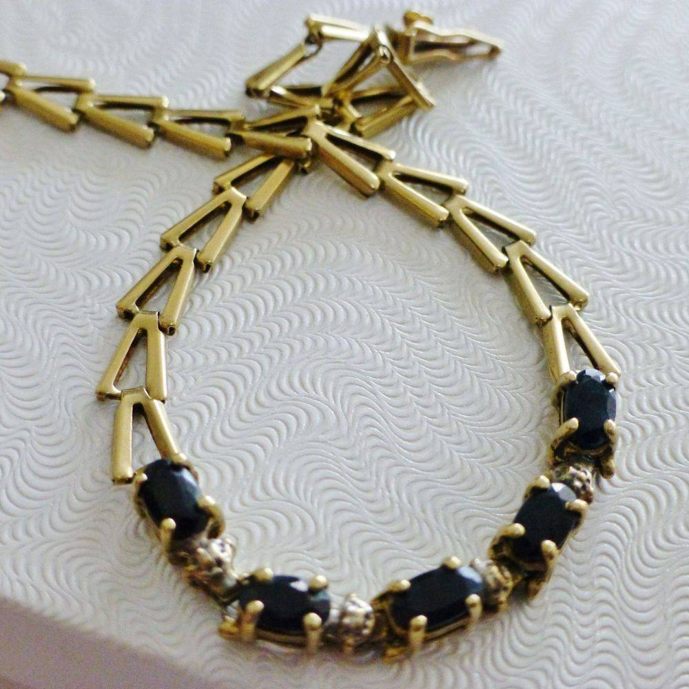 closeup picture of a yellow gold triangle link bracelet with oval cut blue sapphires