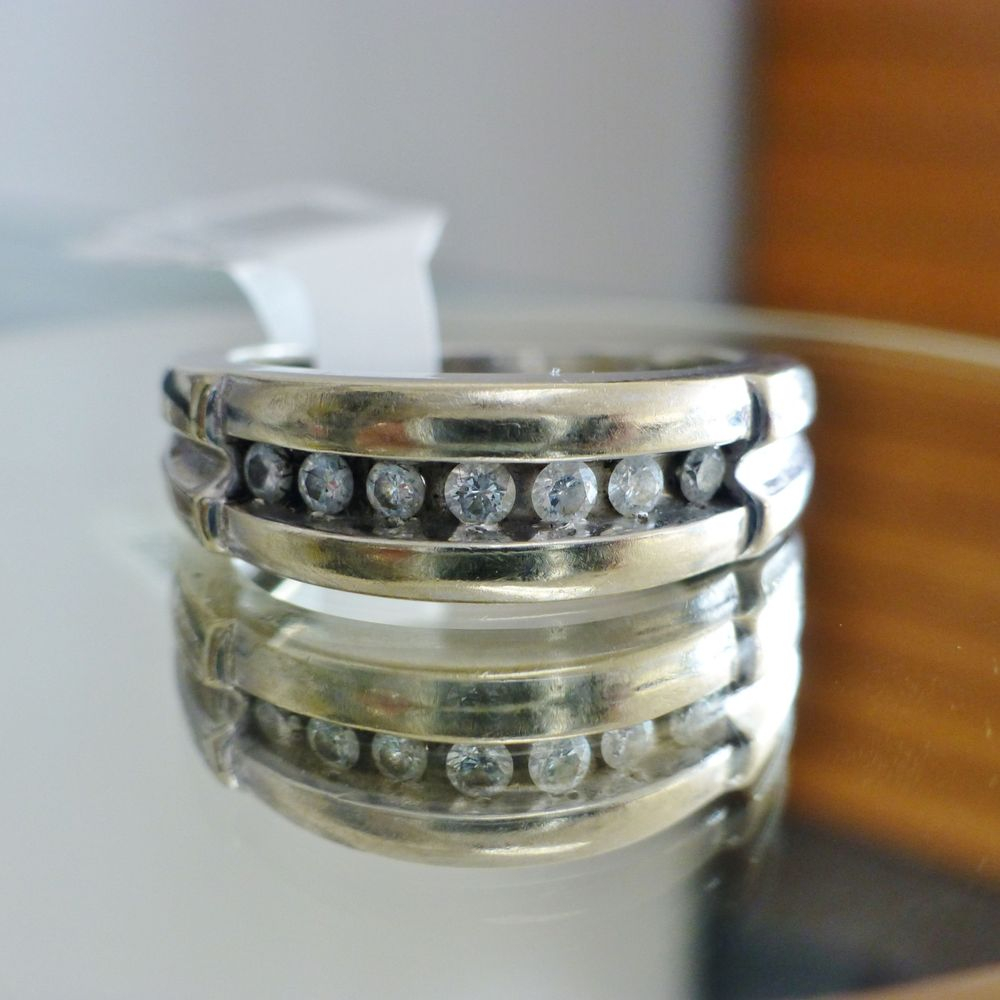close up picture of a white gold men's wedding band with 7 round cut channel set diamonds
