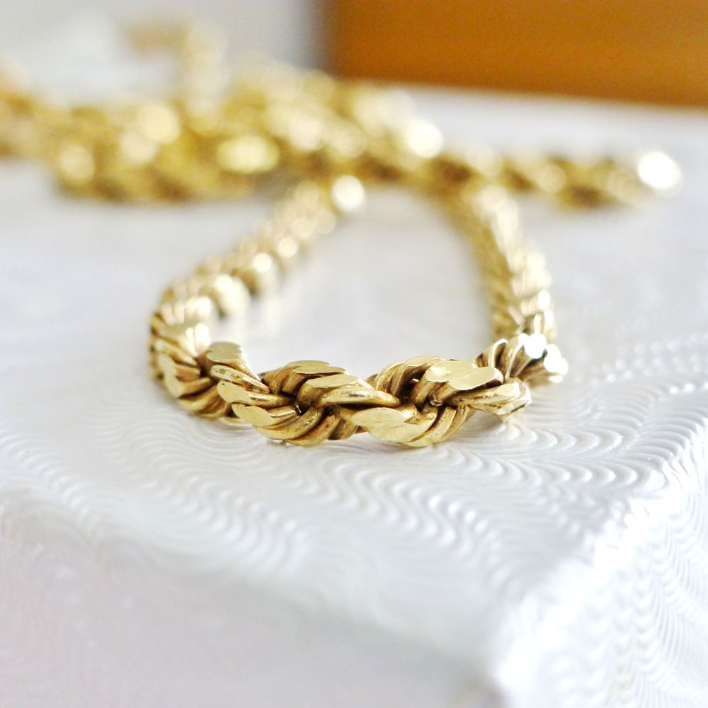 Close up picture of a yellow gold twisted rope chain necklace on a white box