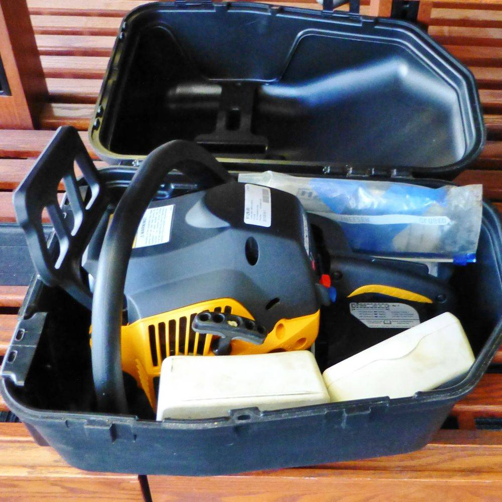 black and yellow chain saw inside of a case sitting on a shelf