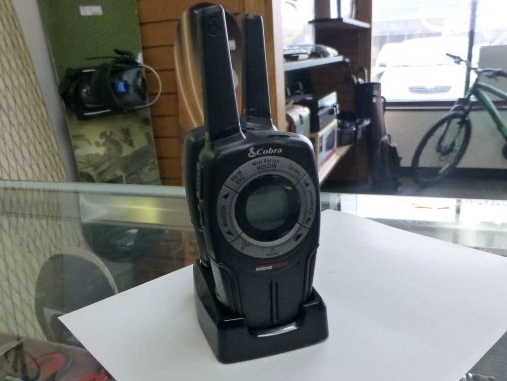 A set of two black walkie talkies on a charging base