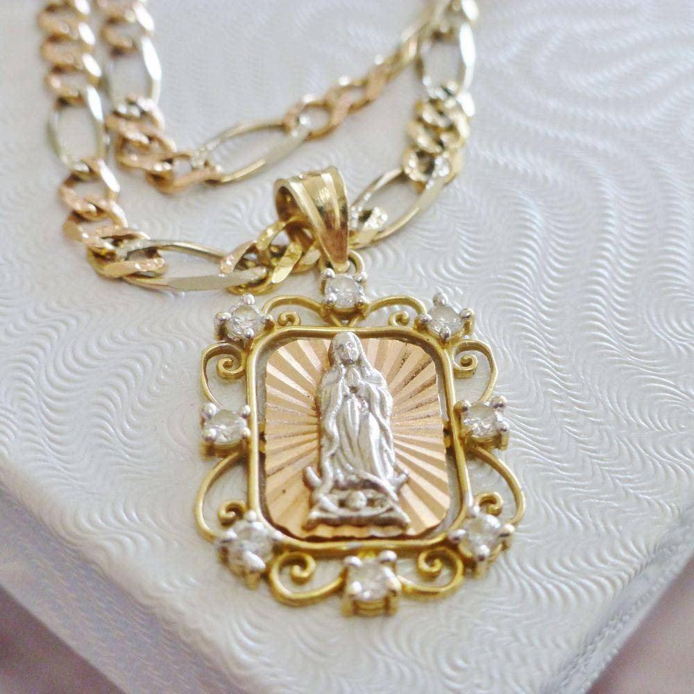 Close up picture of a tri color 14k gold filigree and cubic zirconia framed rectangular Lady of Guadalupe Virgin Mary Charm on a Figaro Necklace