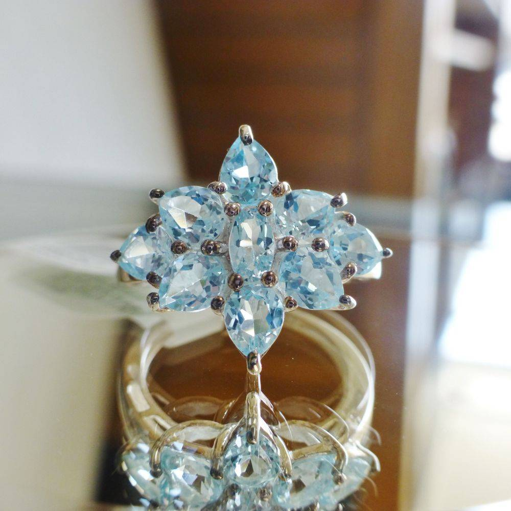 Closeup picture of a sterling silver ring with oval and pear cut blue topaz gemstone prong set in a flower design