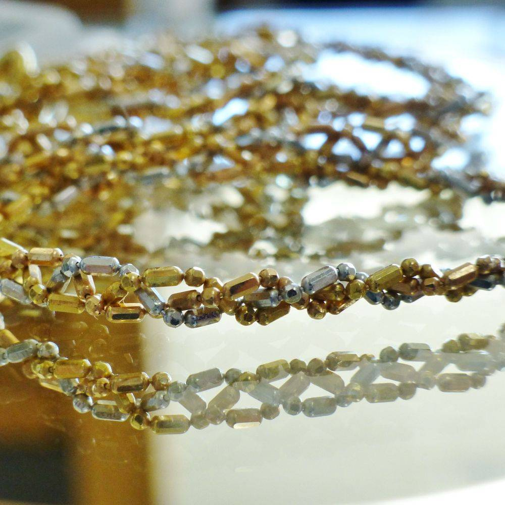 close up picture of bead and bar link triple strands braided necklace in yellow and white gold