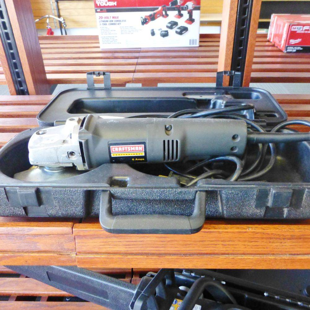 Close up picture of a gray and black Craftsman corded angle grinder in carrying case on a wooden shelf