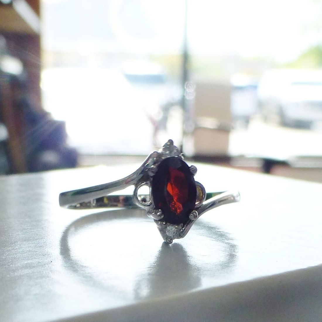 White Gold Ring Holding An Oval Red Garnet Gemstone And Side Diamond Accents