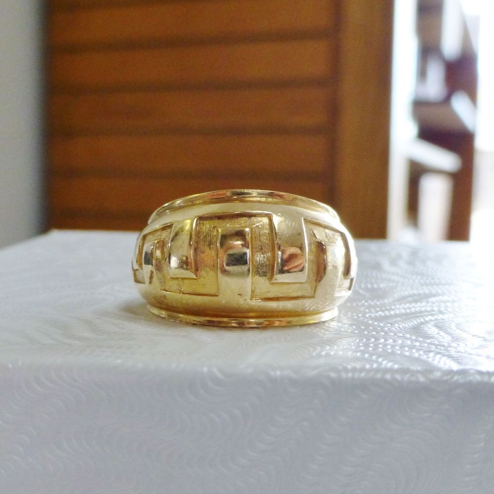 close up picture of a yellow gold dome ring with a carved Greek Design