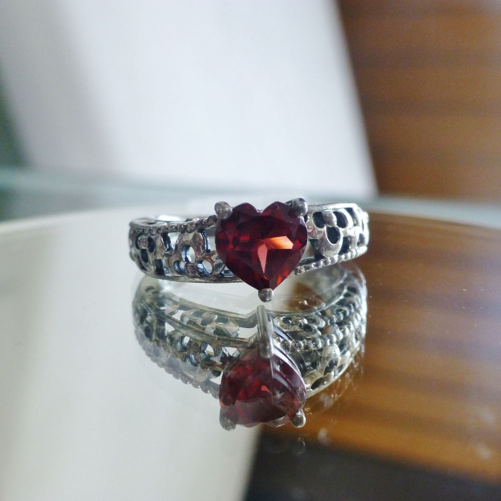 close up picture of a sterling silver filigree ring with a heart cut garnet prong set and centered