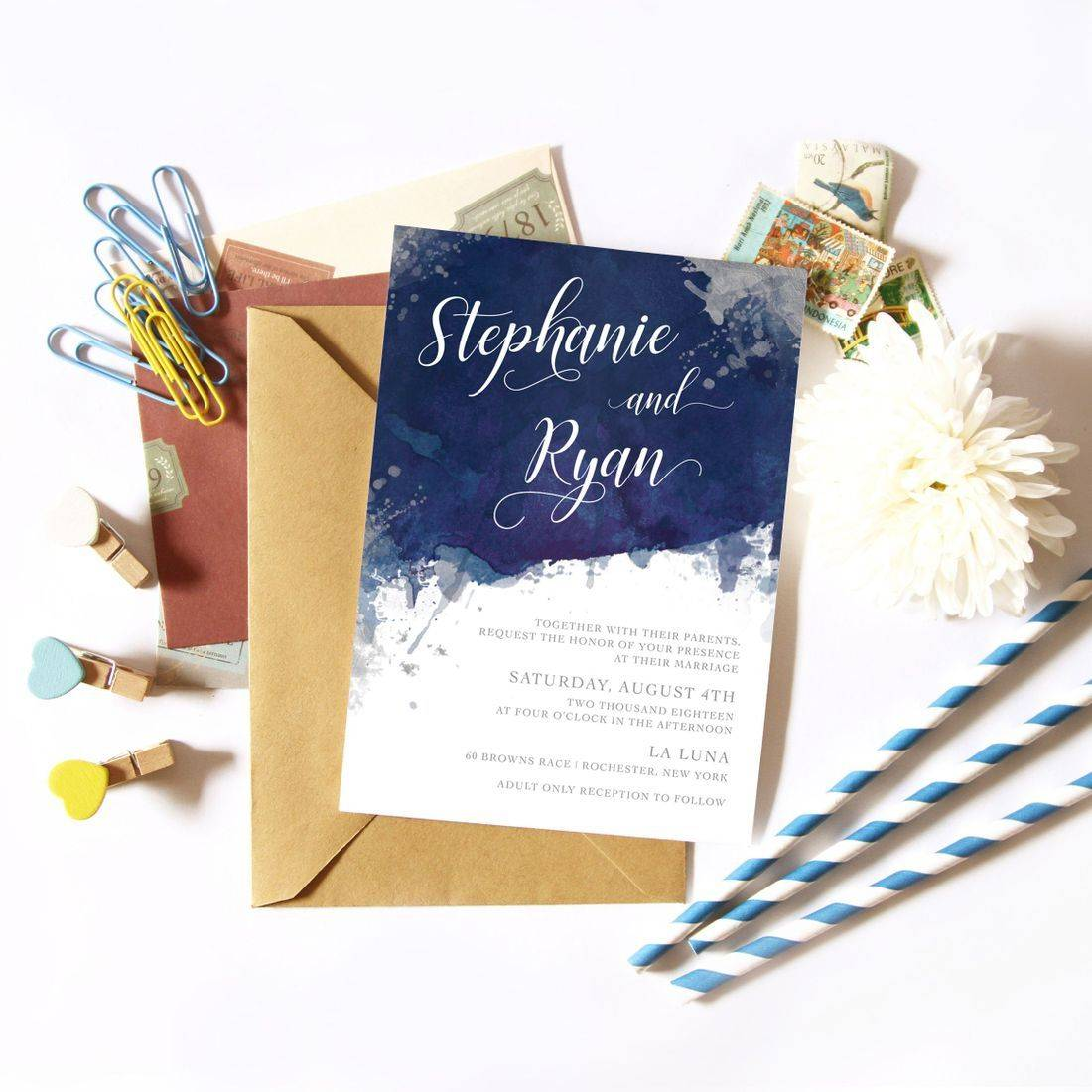Paint splatter invitation flat lay with vintage stamps and flower