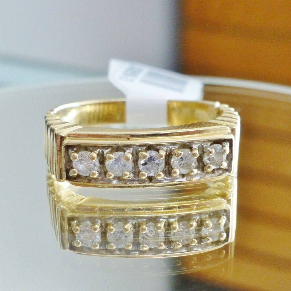 Closeup picture of a yellow gold five stone men's diamond rolex ring
