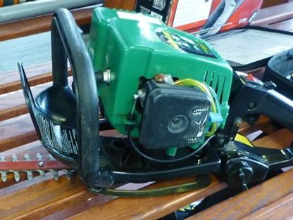 Green Weed Eater Hedge Trimmer on a Wooden Shelf