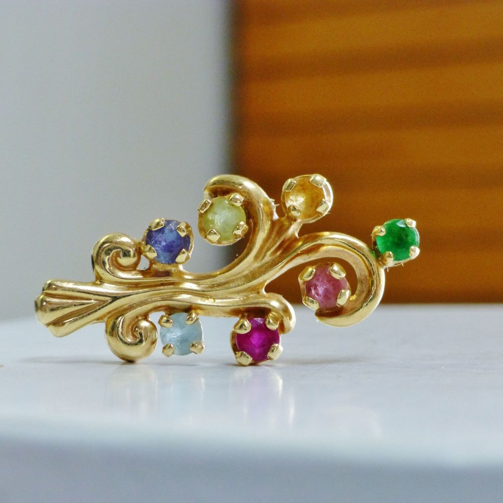 yellow gold swirling pendant with round cut multi color gemstones