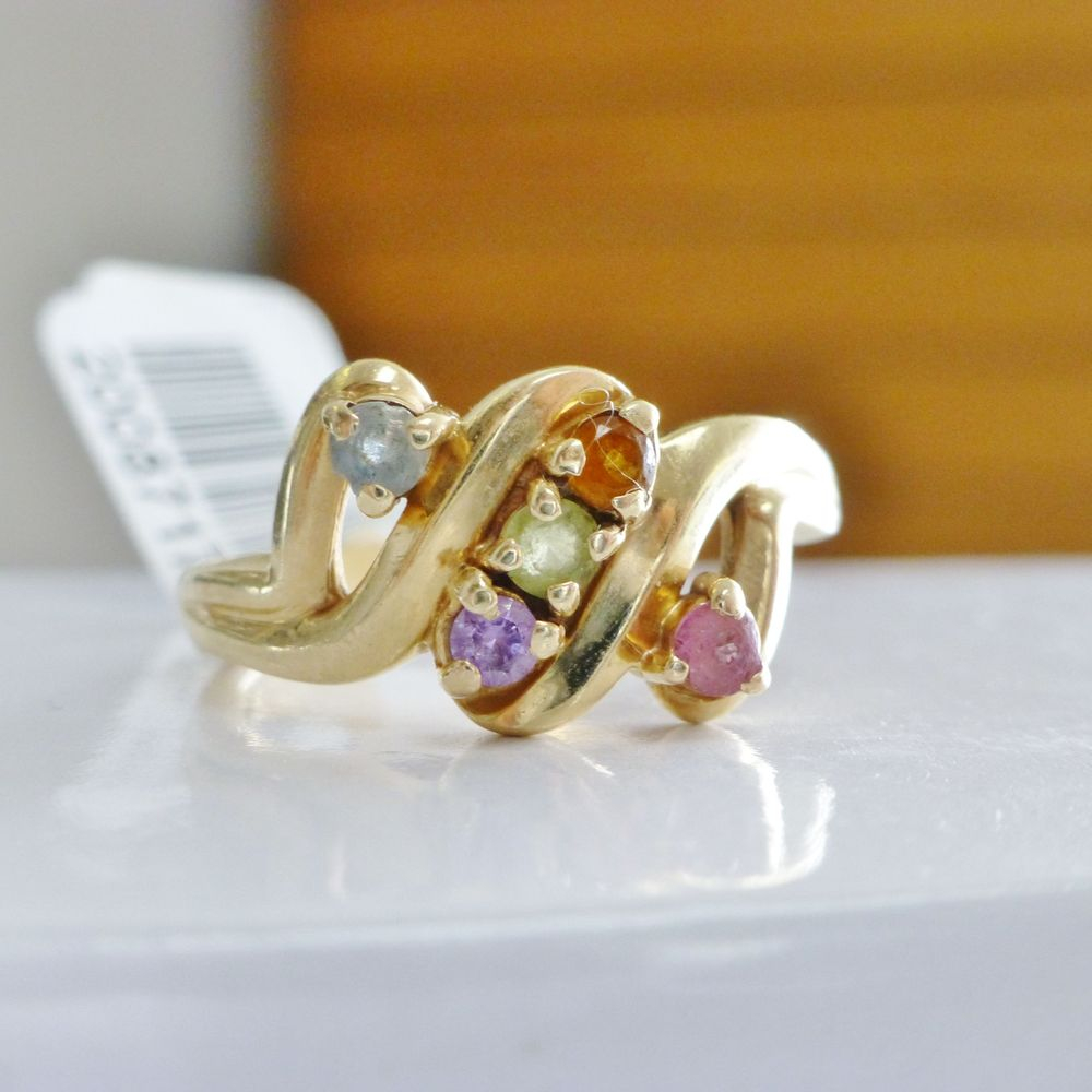 Closeup picture of a yellow gold mother's ring with blue, purple, pink green and orange stones