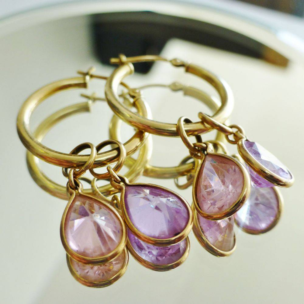 closeup picture of a pair of yellow gold hoops with pear cut pink and purple cubic zirconia dangles