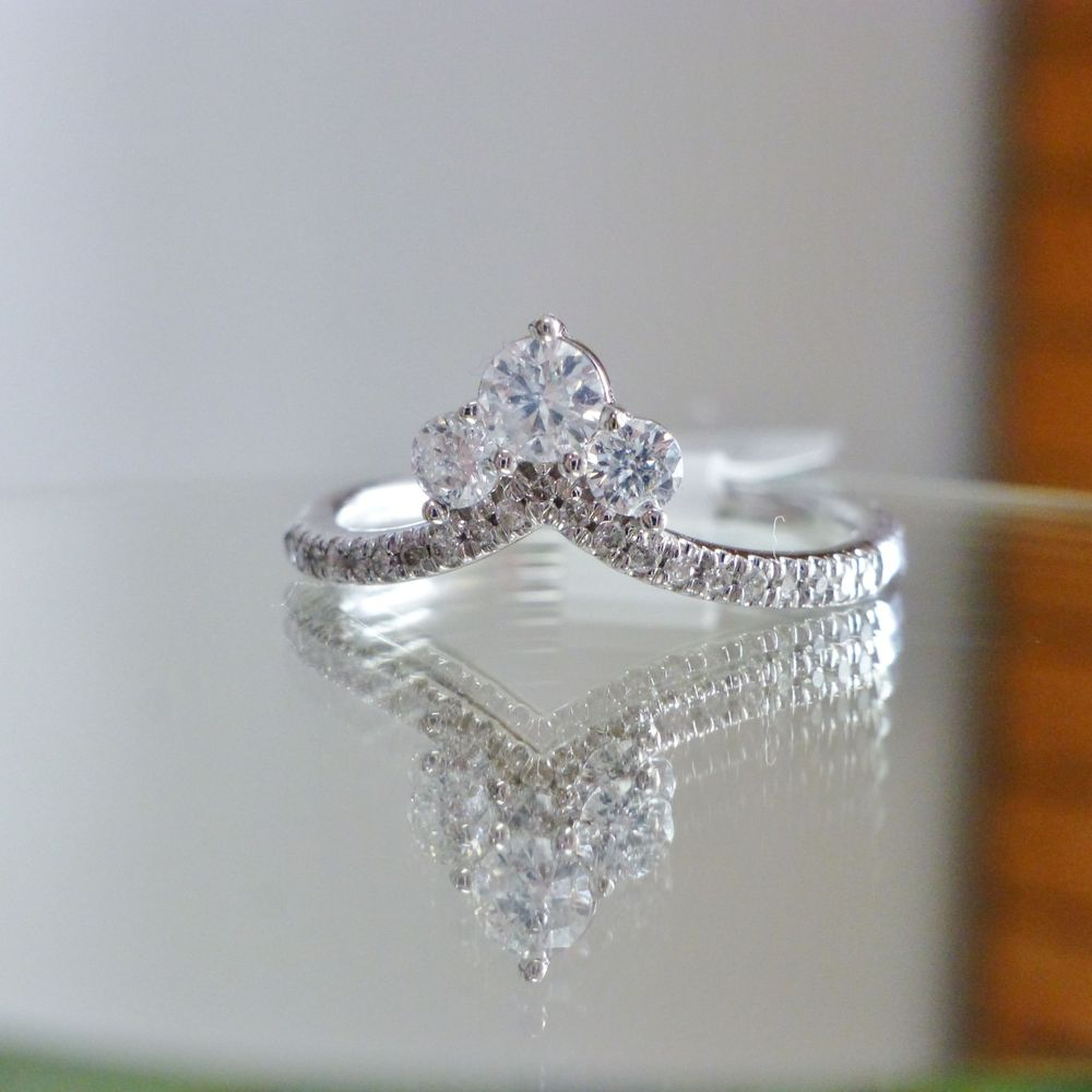close up picture of a white gold chevron ring with round cut daimonds