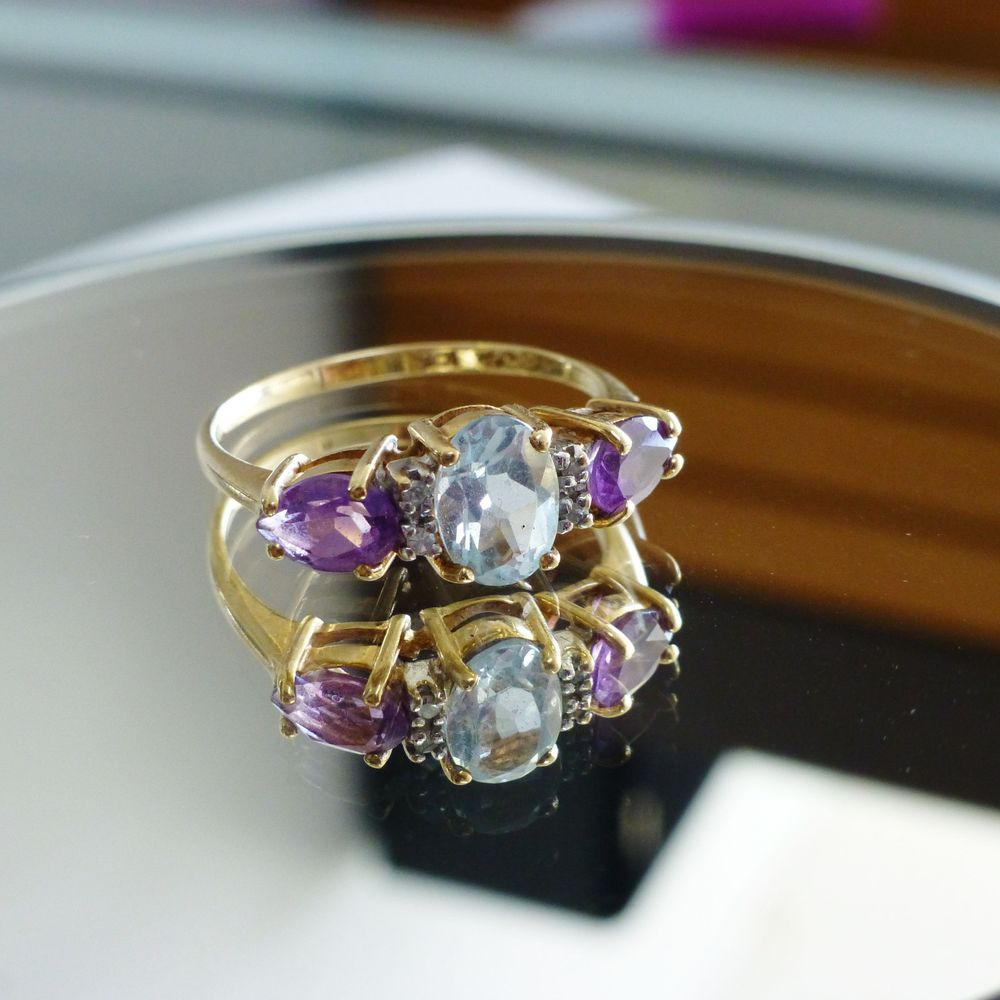 Closeup picture of a yellow gold ring with an oval cut aquamarine and two purple pear cut amethysts