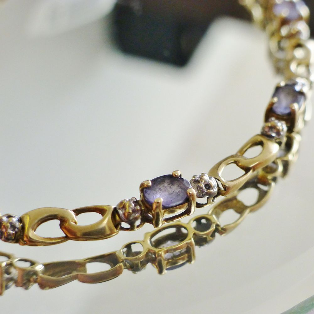 closeup picture of a yellow gold oval cut tanzanite diamond accent link bracelet