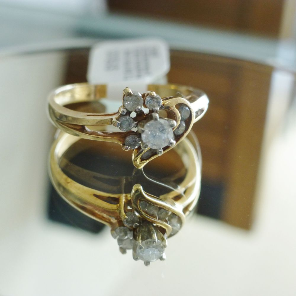 close up picture of a yellow gold ring round cut solitaire ring with channel and prong set diamond heart frame