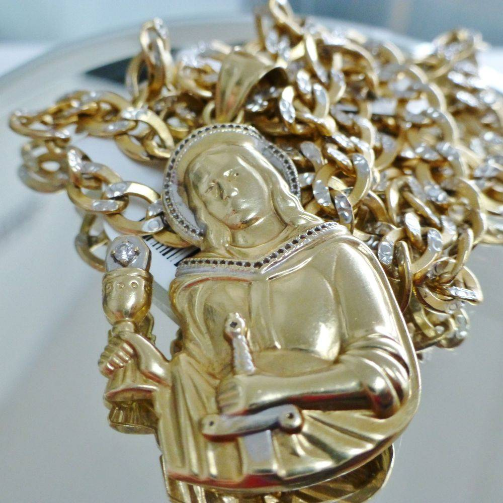 close up picture of a two tone gold diamond accent Saint Barbara pendant on a diamond cut curb link chain
