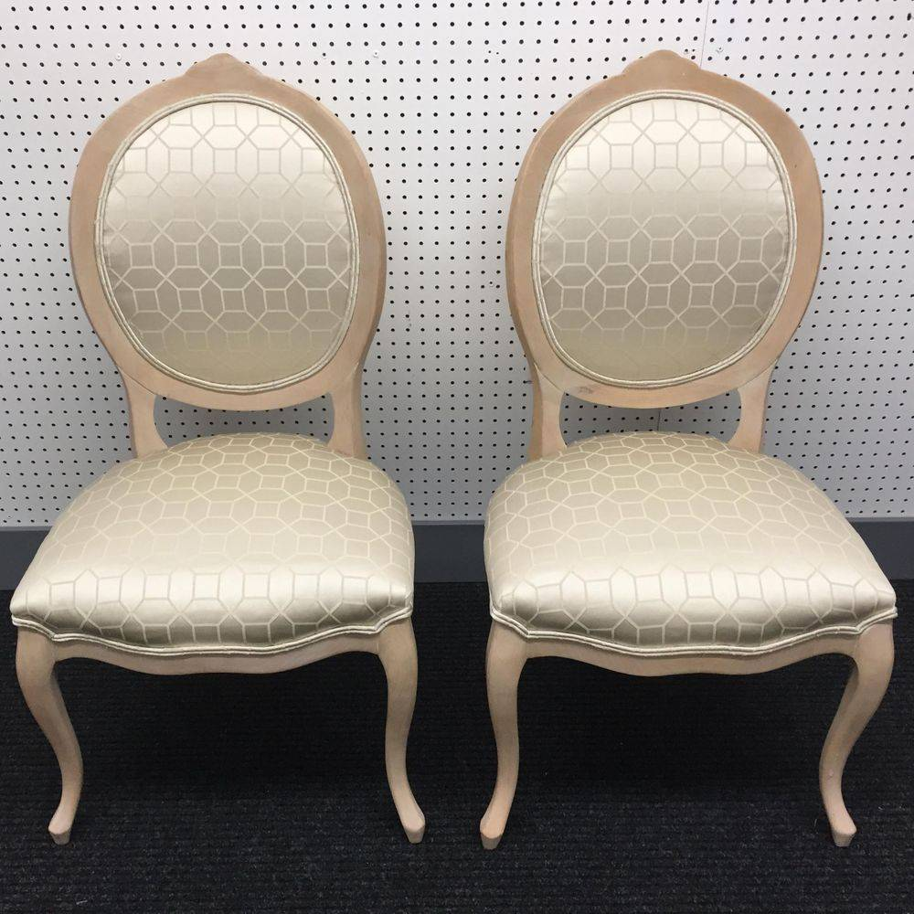 two matching chairs done in a ivory satin material