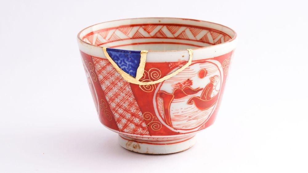 kintsugi example on broken japanese teacup fixed with gold enamel