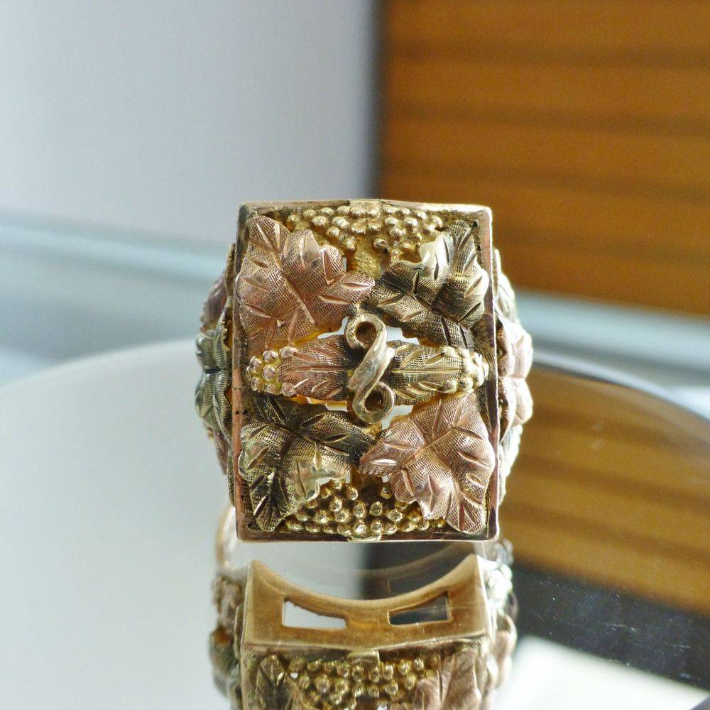 closeup picture of a rose and yellow gold ring with vines and leaves design