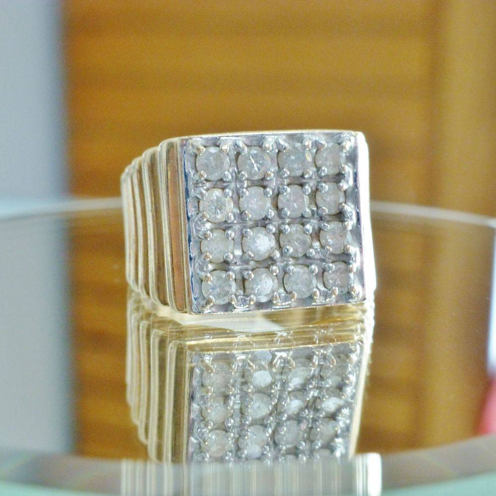 close up picture of a mens yellow gold stepped shank ring with a square top diamond cluster