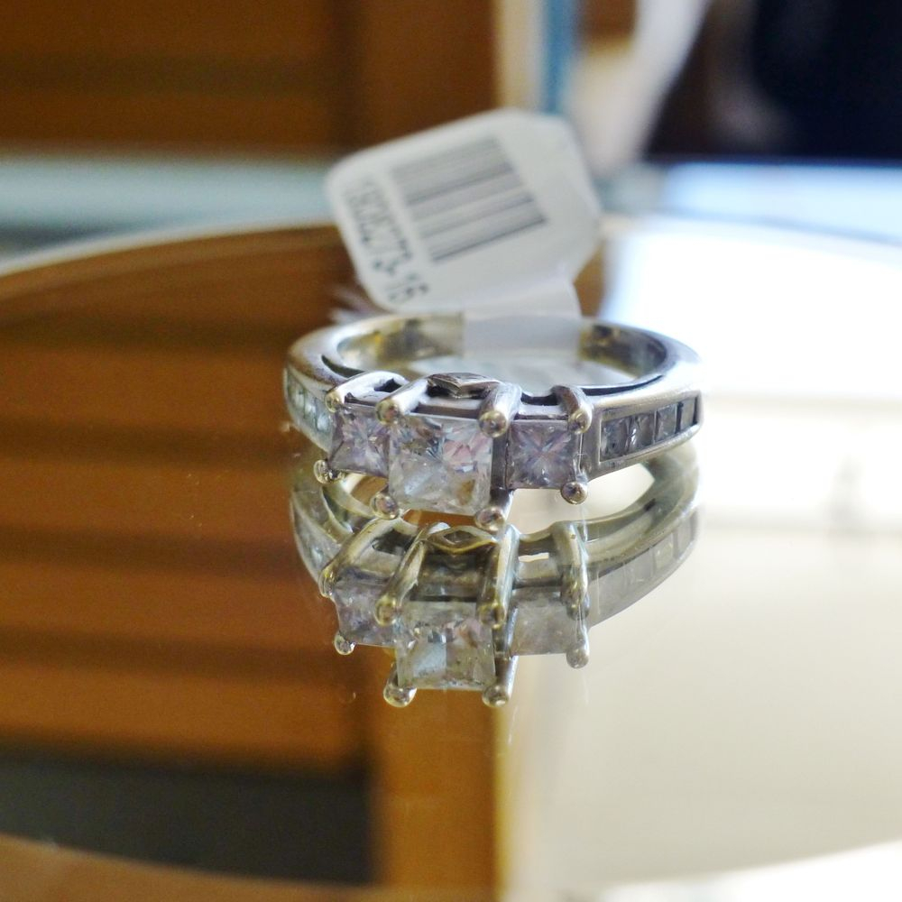 close up picture of a white gold three stone engagement ring with prong set princess cut diamonds