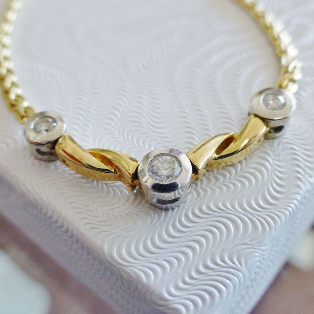 Closeup Picture a braided yellow gold necklace with three round cut bezel set diamond station center
