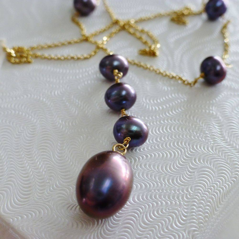 closeup picture of a yellow gold aubergine tahitian fixed pearl lariat necklace