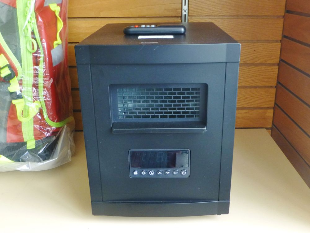 close up picture of a black Magnavox space heater cabinet with remote on a shelf