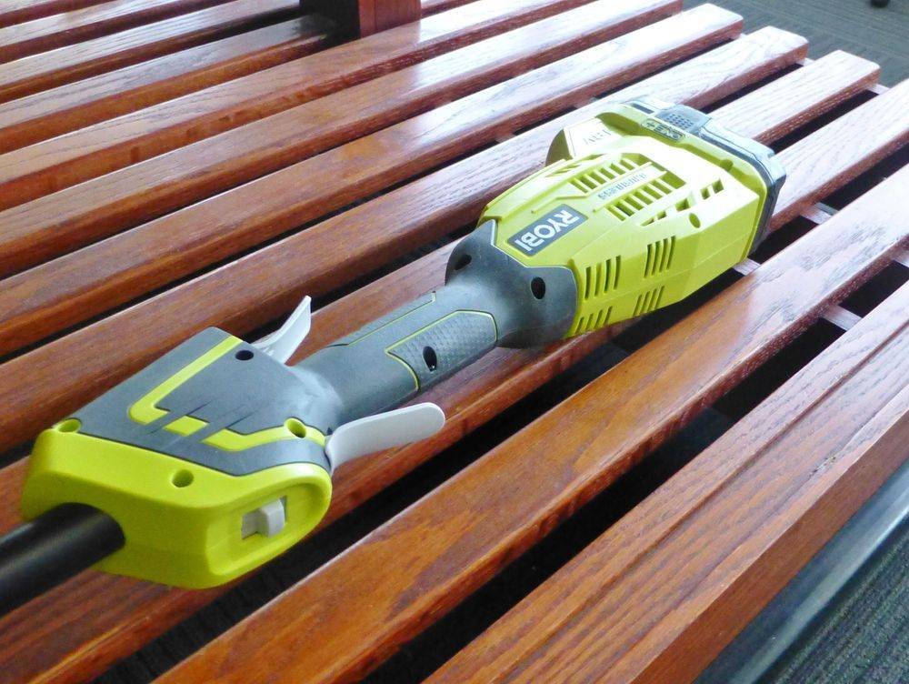 Ryobi 18V string trimmer laying on a wooden shelf