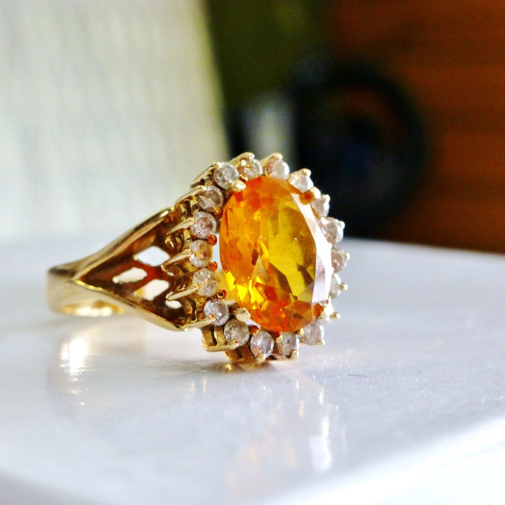Oval Cut Yellowish Orange Madeira Citrine gemstone framed by a diamond halo in a yellow gold ring