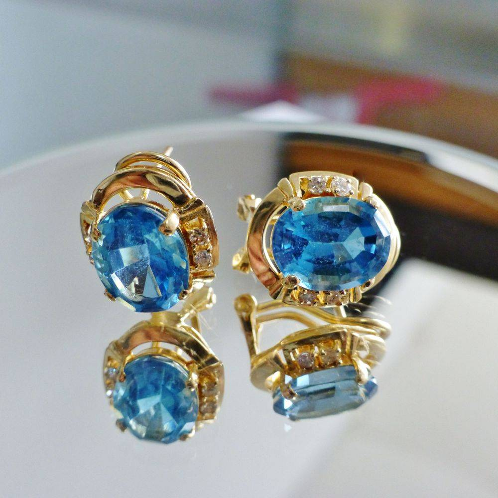 closeup picture of yellow gold oval swiss blue topaz with round white sapphire earrings