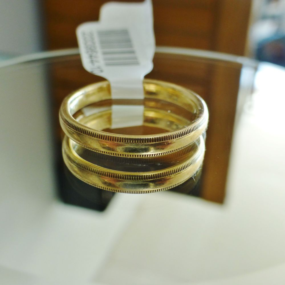 close up picture of a yellow gold men's wedding band with a coin edge design