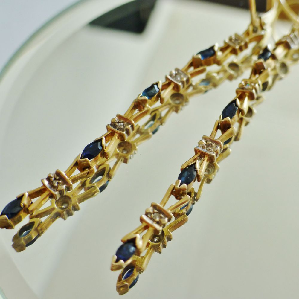 pair of yellow gold linear drop earrings with blue sapphire and diamonds
