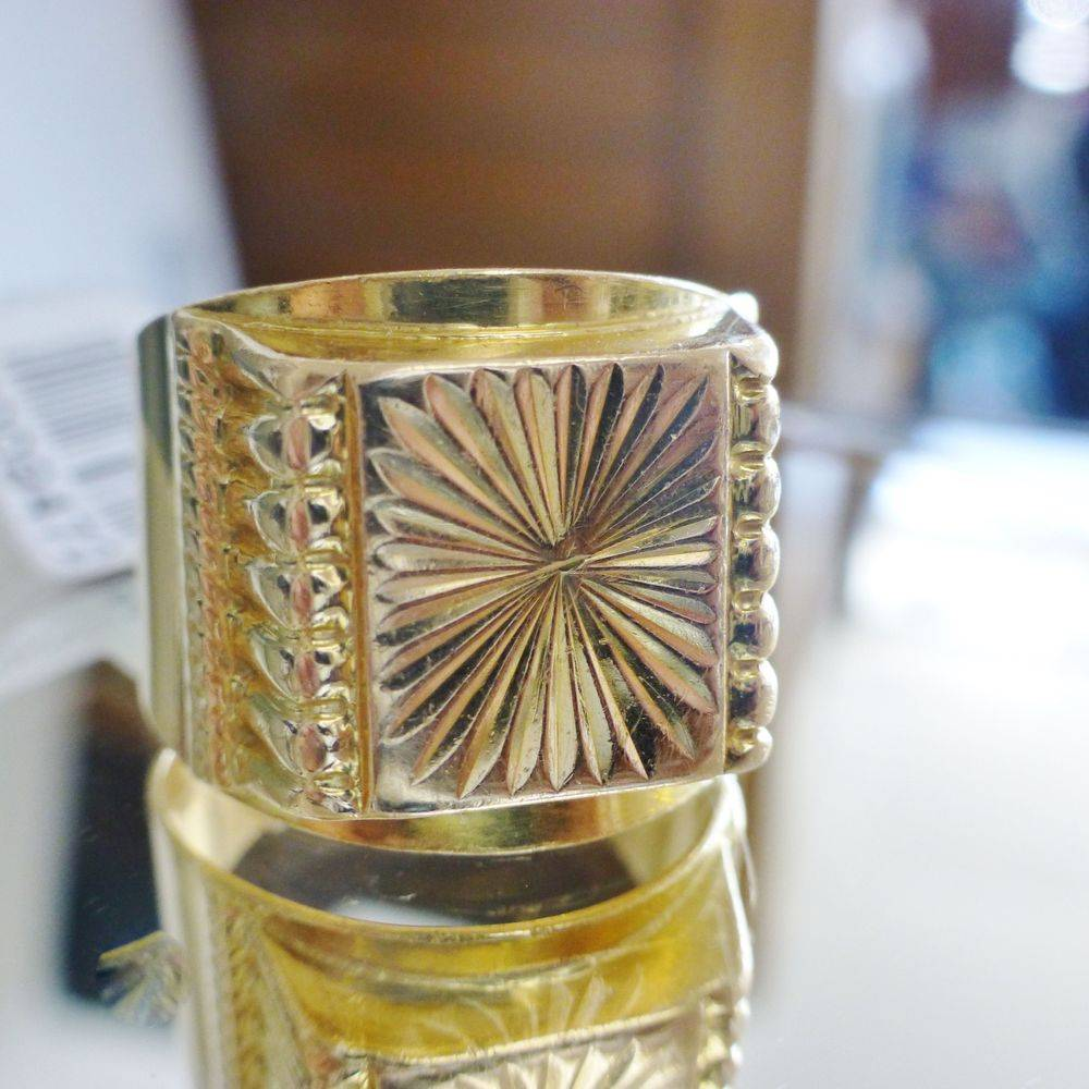 close up picture of a yellow gold men's square top textured starburst design signet pinky ring
