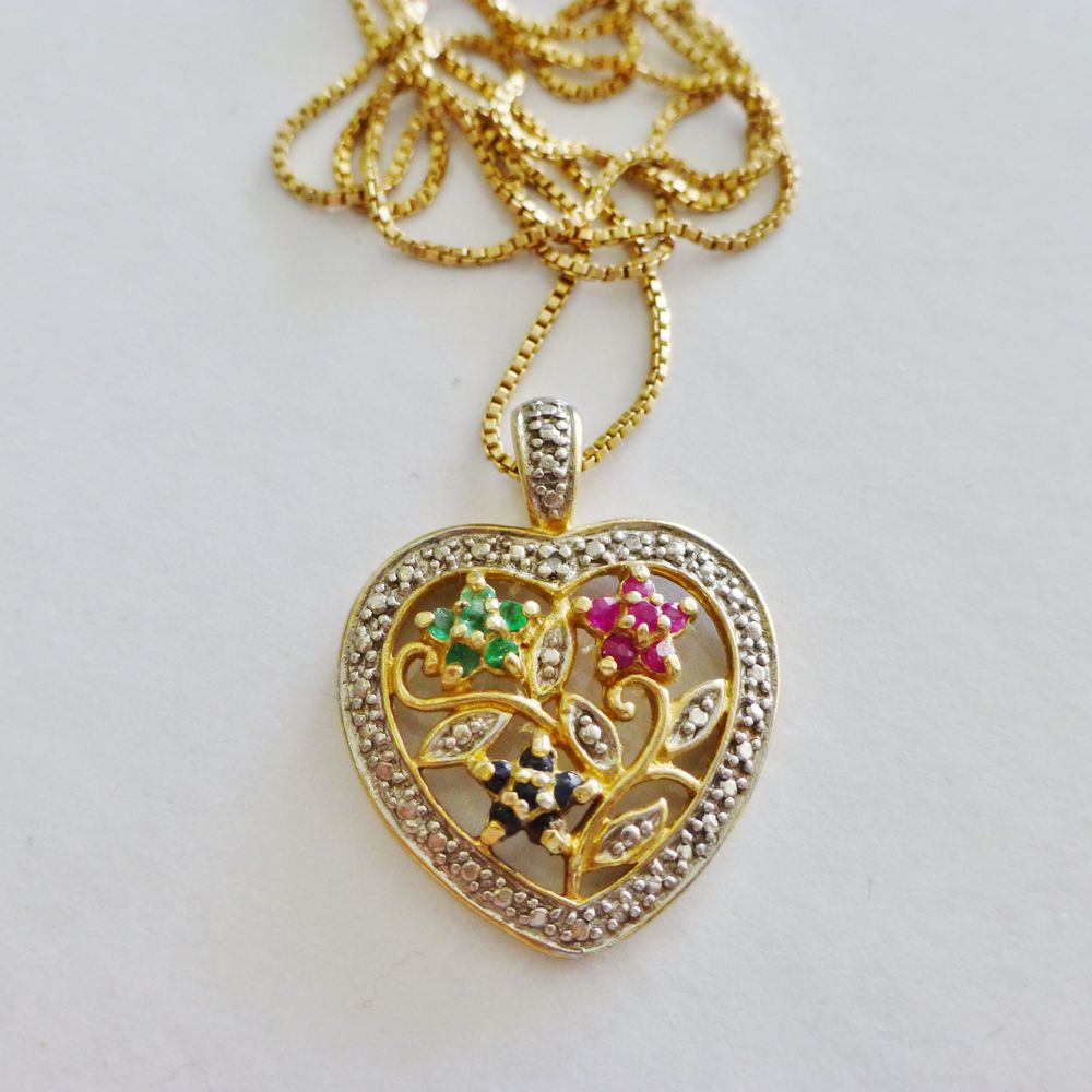 Ruby, Emerald and Sapphire Flowers inside of a diamond frame shaped heart on a box link necklace in gold