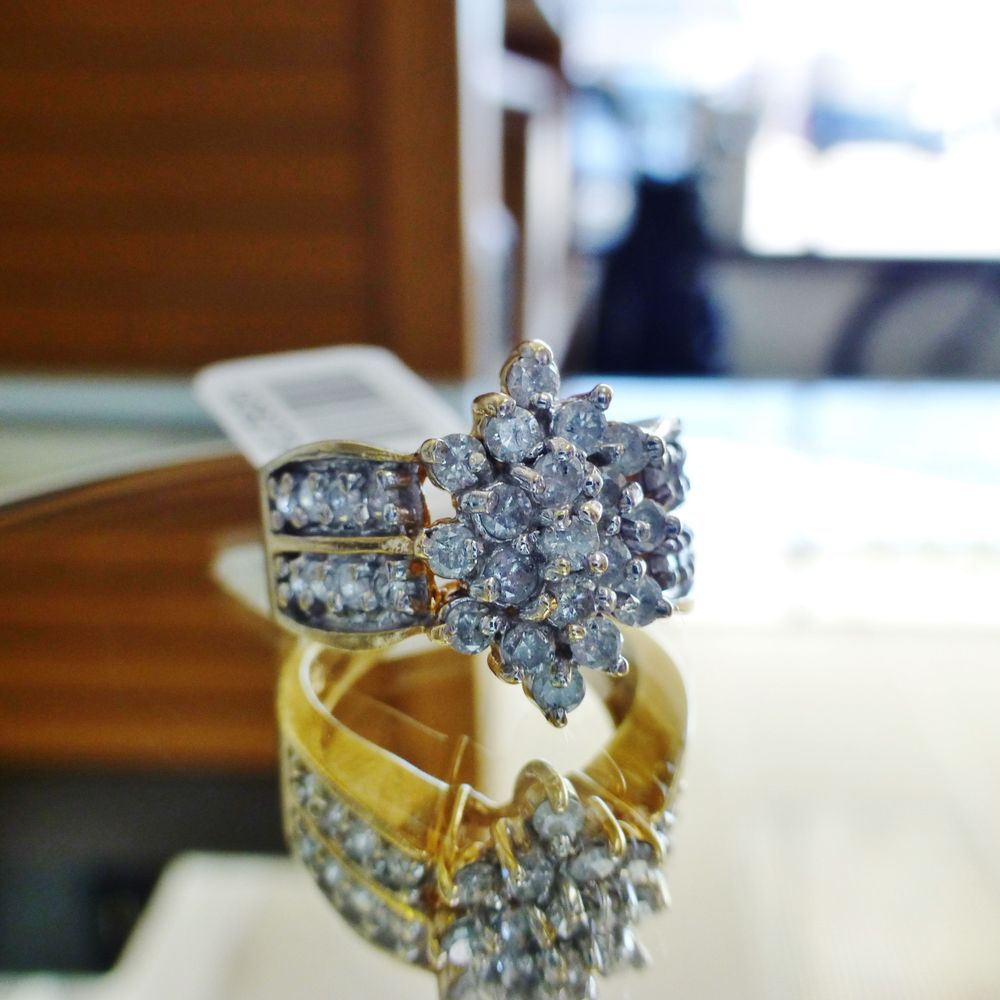 close up picture of a yellow gold wide band ring with marquise shaped diamond cluster